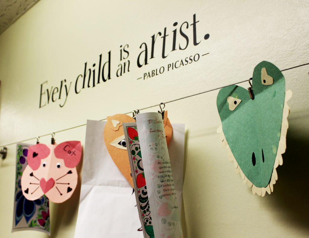 Children's artwork on wall with Picasso quote, every child is an artist