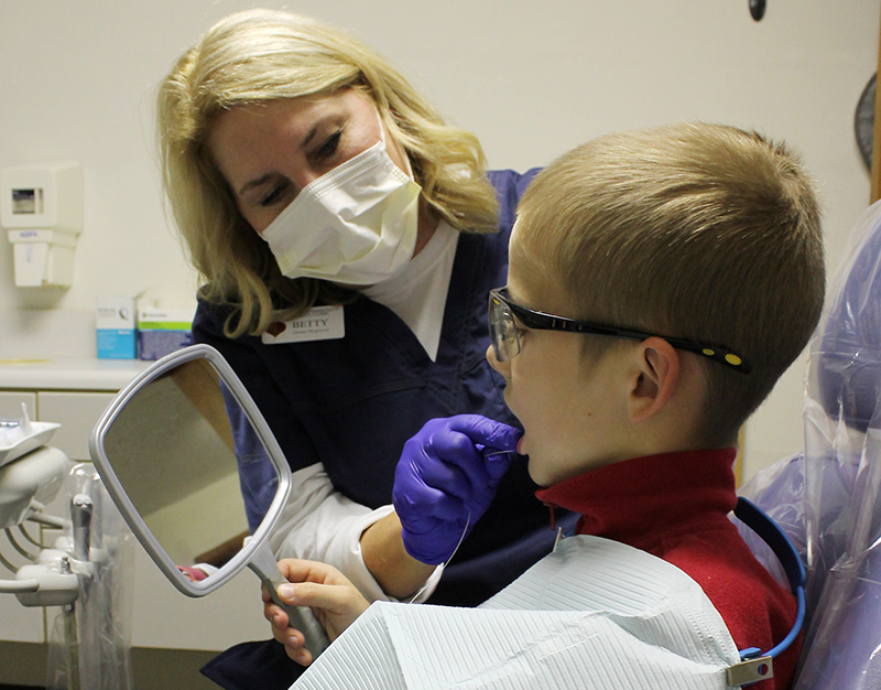 Dental hygienist performing cleaning on child