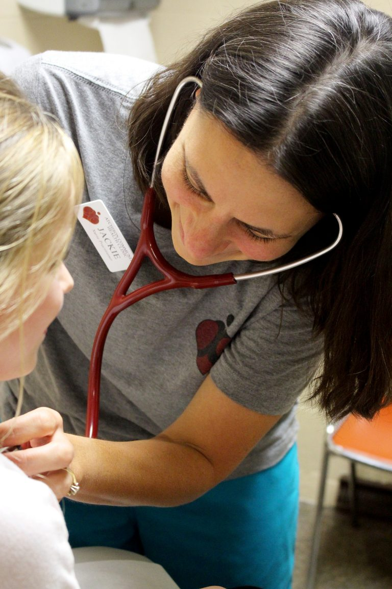 Nurse with stethoscope listening to a child's heartbeat