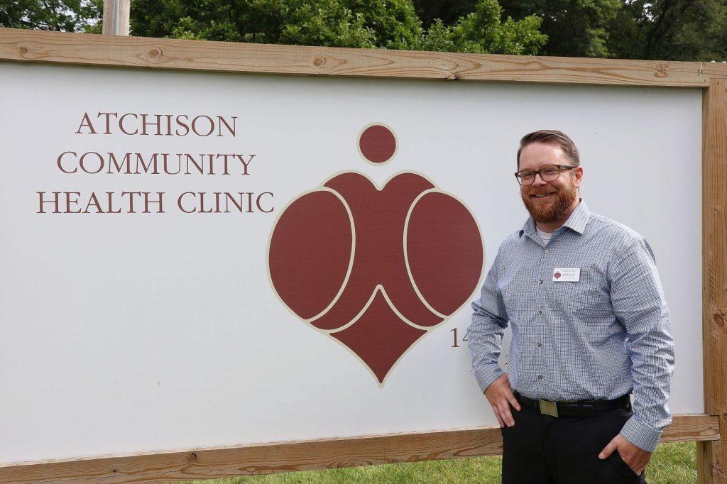Stevie Durkin posing next to ACHC clinic sign