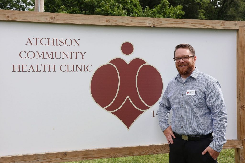 Stevie Durkin posing next to ACHC clinic sign