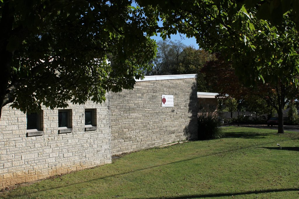 Exterior side view of grey stone ACHC clinic building