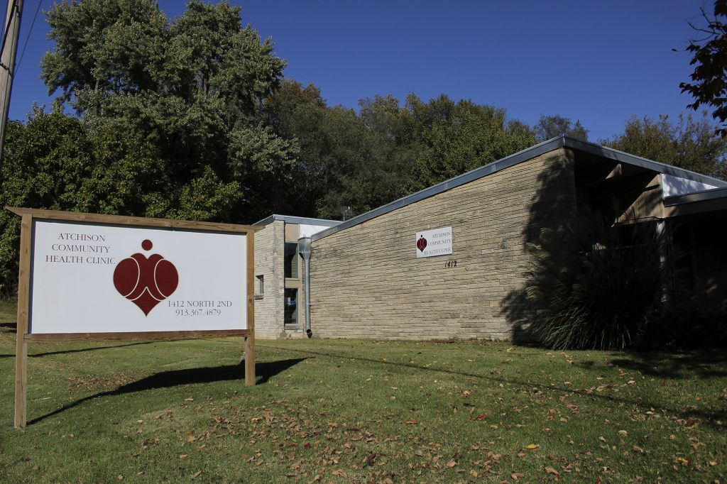 Exterior view of clinic building with clinic sign in foreground