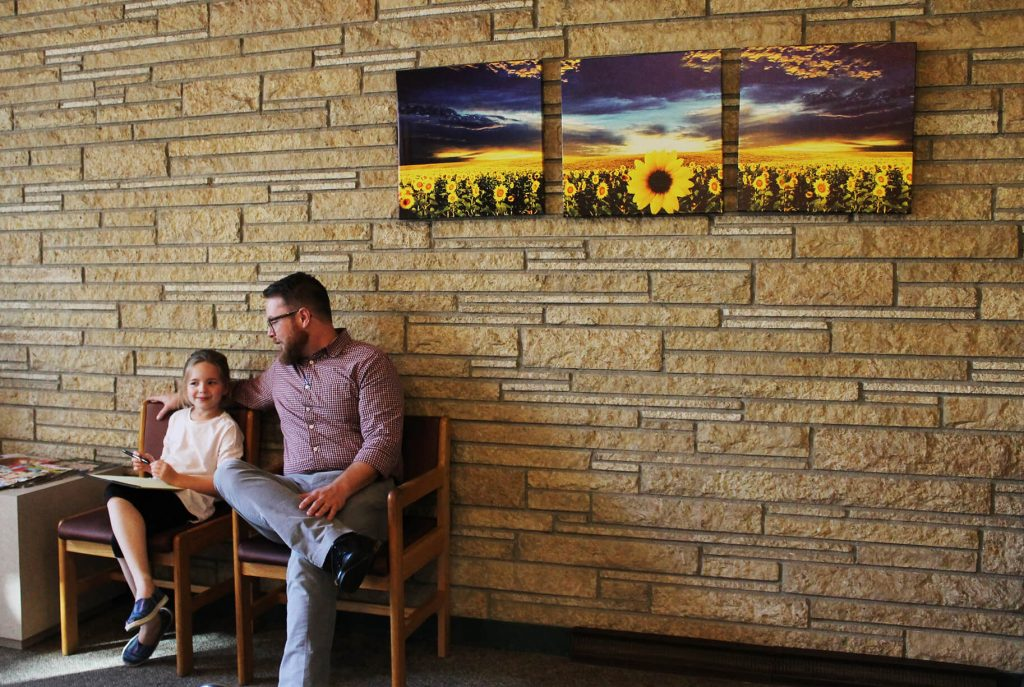 Man and child in waiting room in front of stone wall